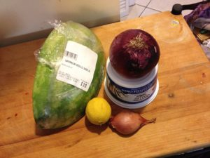 A quarter of a smallish watermelon, a red onion, a lemon, and a lobe of shallot sitting pertly on a cutting board.